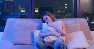 Woman watch horror movies. Young woman watch horror movies with popcorn at night stock photography