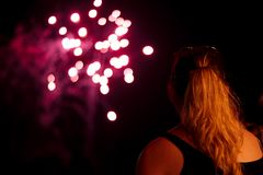 A young woman watches fireworks stock images