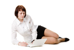Young woman watches at a laptop. Young woman sitting on the floor and watches at a laptop, isolated on a white background Stock Photography
