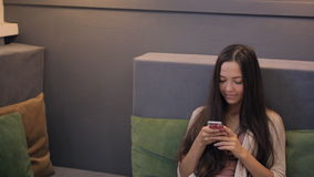 Young woman watches news of social networking on her smartphone. stock video footage