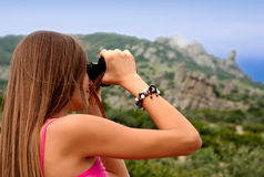 Young woman watching through binoculars Royalty Free Stock Image