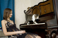 The young woman is watching cat walking on piano. Funny situaition Stock Photography