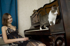 The young woman is watching cat walking on piano. Funny situaition Royalty Free Stock Photo