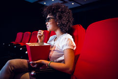 Young woman watching a 3d film and eating pop corn Stock Photo