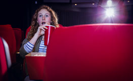 Young woman watching a film and drinking a soda Royalty Free Stock Image