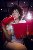 Young woman watching a film and drinking a soda Stock Photography