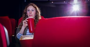 Young woman watching a film and drinking a soda Stock Images