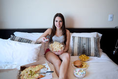 Young woman watching a funnt movie on tv in bed Royalty Free Stock Photos