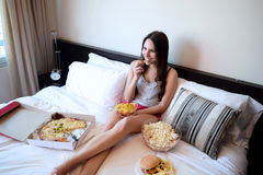 Young woman watching a funnt movie on tv in bed Royalty Free Stock Photography
