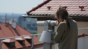 Woman is watching landmarks of city by telescope