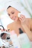 Young woman watching in the mirror and putting on makeup Royalty Free Stock Photos