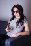 Young woman watching movie in 3d glasses at home Royalty Free Stock Images