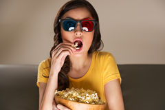 Young woman watching movie at home. Young woman with popcorn and 3d glasses watching movie at home Royalty Free Stock Photography