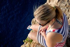 Young woman is watching ocean and sitting on a cliff. Top view Stock Images