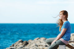 Young woman watching the ocean. Sitting on a wooden railing above a rocky shoreline with a lovely smile Royalty Free Stock Photo