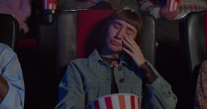 Young woman watching sad drama movie in cinema and hugging popcorn bowl. Hipster girl crying and wiping tears with hand