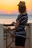 Young woman watching sea sunset. Young woman in hat and cute summer dress standing at the balcony railing looking at picturesque sea sunset or sunrise, back view Stock Images