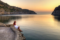 Young woman watching sunrise. Beautiful young woman watching sunrise on Anthony Quinn Bay. HDR photography of greek landscape - Rhodes Royalty Free Stock Photo