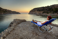 Young woman watching sunrise. Beautiful young woman watching sunrise on Anthony Quinn Bay. HDR photography of greek landscape - Rhodes Stock Photo