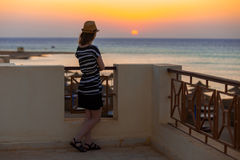 Young woman watching sunrise. Young woman in hat and cute summer dress standing in feminine carefree pose at the balcony with beautiful sea scenery, watching Royalty Free Stock Photos