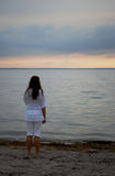 Young woman watching the sunset. Woman watching the sunset alone Royalty Free Stock Photos