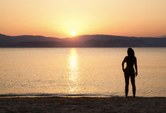 Young woman watching sunset. On the beach Stock Images