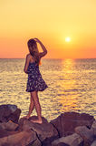 Young Woman Watching Sunset. Girl Watching Sunset in Back View. Dressing in patterned sundress, barefoot, waving a hand,  a pretty girl is standing on rocks on Royalty Free Stock Photos