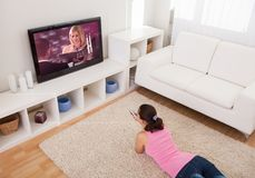 Young woman watching television Royalty Free Stock Photos