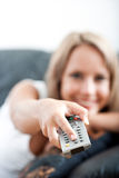 Young woman watching television with a remote Stock Photos