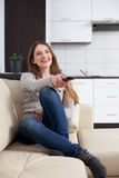 Young woman watching television on sofa Royalty Free Stock Photo