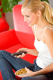 Young woman watching TV. Young happy smiling woman watching TV at home Royalty Free Stock Photo