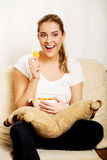 Young woman watching TV and eating chips Stock Photos