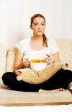 Young woman watching TV and eating chips Royalty Free Stock Images
