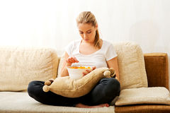 Young woman watching TV and eating chips Stock Image