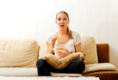 Young woman watching TV and eating chips Royalty Free Stock Photography