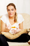 Young woman watching TV and eating chips.  Royalty Free Stock Photography