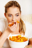 Young woman watching TV and eating chips.  Royalty Free Stock Images