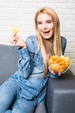 Young woman watching TV and eating chips on sofa Royalty Free Stock Images