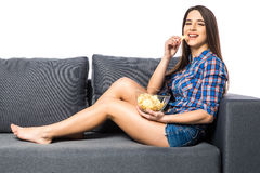Young woman watching TV and eating chips on white background Stock Photography