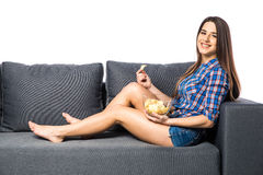 Young woman watching TV and eating chips on white background. Young woman watching TV and eating chips Royalty Free Stock Photo