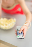 Young woman watching tv and eating popcorn Royalty Free Stock Photo