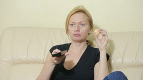 Young woman watching TV at home. eat a tangerine stock video
