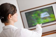 Young woman watching tv at home Stock Images