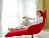 Young woman watching tv at home. Happy young woman watching tv at modern home livingroom Royalty Free Stock Image