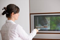 Young woman watching tv at home. Happy young woman watching tv at modern home livingroom Stock Images