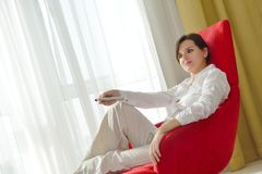 Young woman watching tv at home. Happy young woman watching tv at modern home livingroom Royalty Free Stock Photos