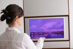 Young woman watching tv at home. Happy young woman watching tv at modern home livingroom Royalty Free Stock Photography