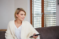 Young woman watching TV at home sittin on sofa Stock Image
