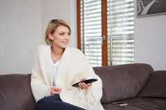 Young woman watching TV at home sittin on sofa Stock Images