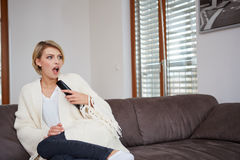 Young woman watching TV at home sittin on sofa Royalty Free Stock Photography